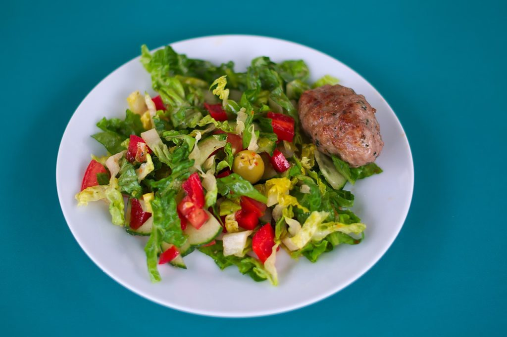 Healthy eating -NewYear goals or resolutions is a picture of a plate of greens with red peppers, tomatoes, olives and a chicken breast