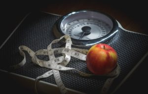 New year goals and resolutions weight loss is a weight scale with a measuring tape anda red apple
